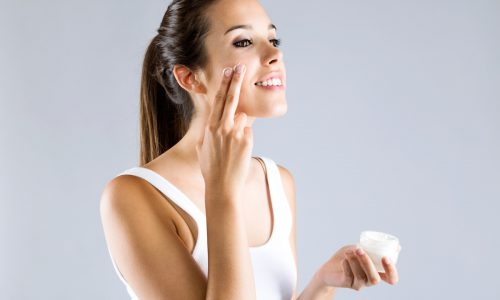 Portrait of pretty young woman applying body cream. Isolated on gray background.